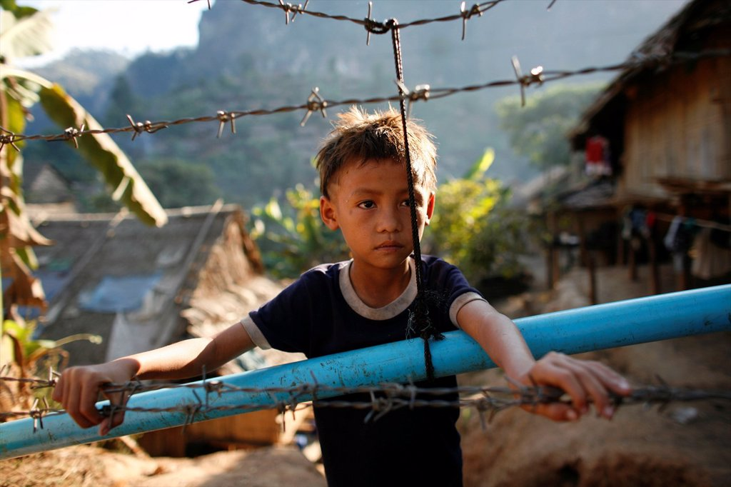 Stock Photo: 1566-980068 Young refugee boy in Mae Sot Around 130,000 Burmese refugees have settled in Thailand due to opression in their homeland of Myanmar Burma Approximately 30,000 refugees now live in Mae Sot western Thailand and receive humanitarian aid Another 200 Burmese r