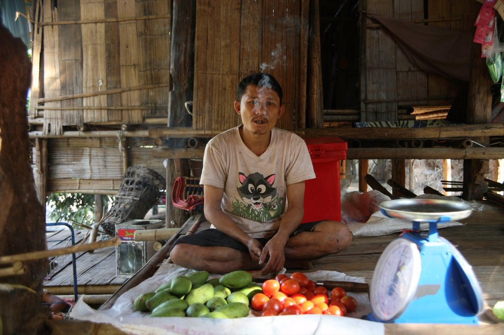 A man sells vegetables in the refugee camp in Mae Sot Around 130,000 Burmese refugees have settled in Thailand due to opression in their homeland of Myanmar Burma Approximately 30,000 refugees now live in Mae Sot western Thailand and receive humanitarian : Stock Photo
