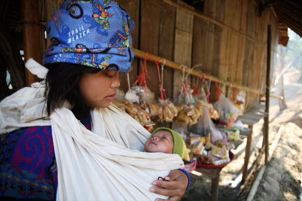 A young girl cradles a baby in Mae Sot refugee camp Around 130,000 Burmese refugees have settled in Thailand due to opression in their homeland of Myanmar Burma Approximately 30,000 refugees now live in Mae Sot western Thailand and receive humanitarian ai : Stock Photo