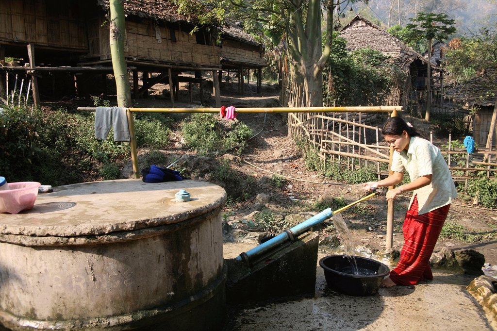 Stock Photo: 1566-980075 A woman gets water from a village pump in Mae Sot refugee camp Around 130,000 Burmese refugees have settled in Thailand due to opression in their homeland of Myanmar Burma Approximately 30,000 refugees now live in Mae Sot western Thailand and receive huma