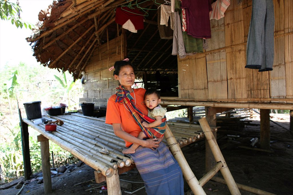 Stock Photo: 1566-980936 A woman with her baby in the displaced persons camp near the Thai border In Myanmar Burma, thousands of people have settled near the border as a result of oppression in their homeland Around 200 Burmese displaced people have settled in La Per Her, a villa