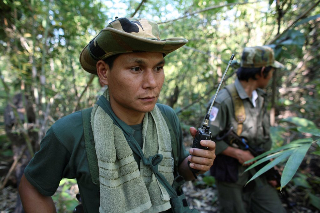 Stock Photo: 1566-980939 Closeup of KNLA soldier with a radio in the jungle near Thailand In Myanmar Burma, thousands of people have settled near the border as a result of oppression in their homeland Around 200 Burmese displaced people have settled in La Per Her, a village on th