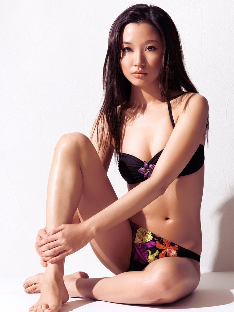 Stock Photo: 1566-982076 Young asian woman wearing a bikini with tropical floral pattern sitting in front of a white wall background in bright sunlight