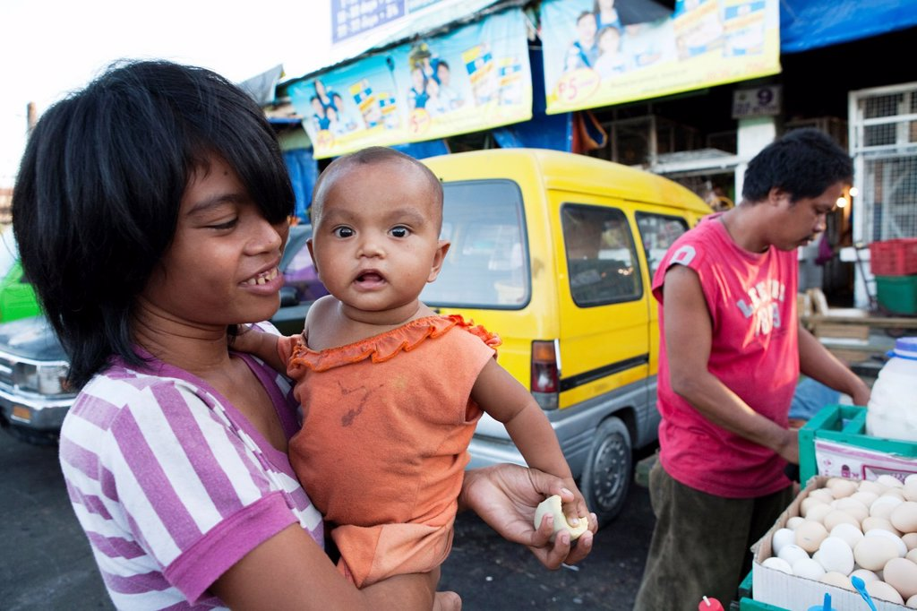 Stock Photo: 1566-982481 Woman with her baby, she is buying Balut, a fertilized duck embryo from a roadside vendor  Carbon Market, Cebu City, Cebu, Visayas, Philippines