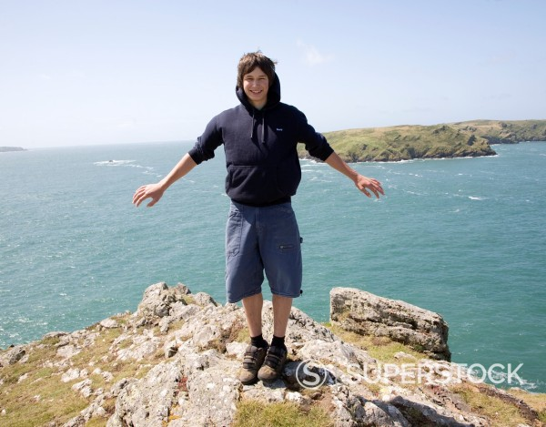 Stock Photo: 1566-985351 Model released picture of teenage boy standing on a cliff being blown by strong wind