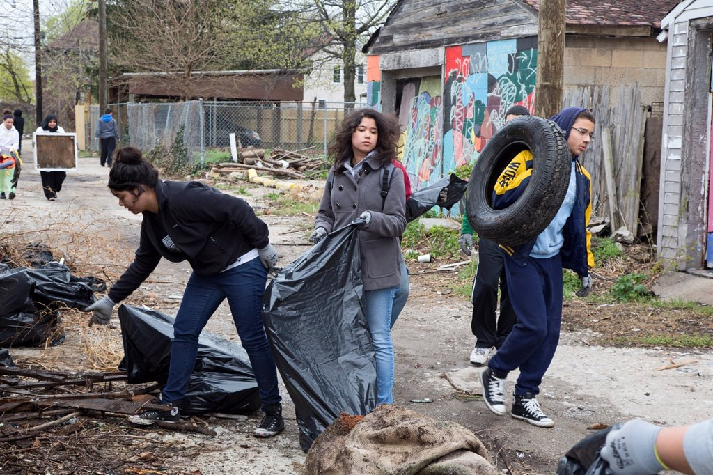 Stock Photo: 1566-985891 Detroit, Michigan - High school and college student volunteers clean trash from an alley