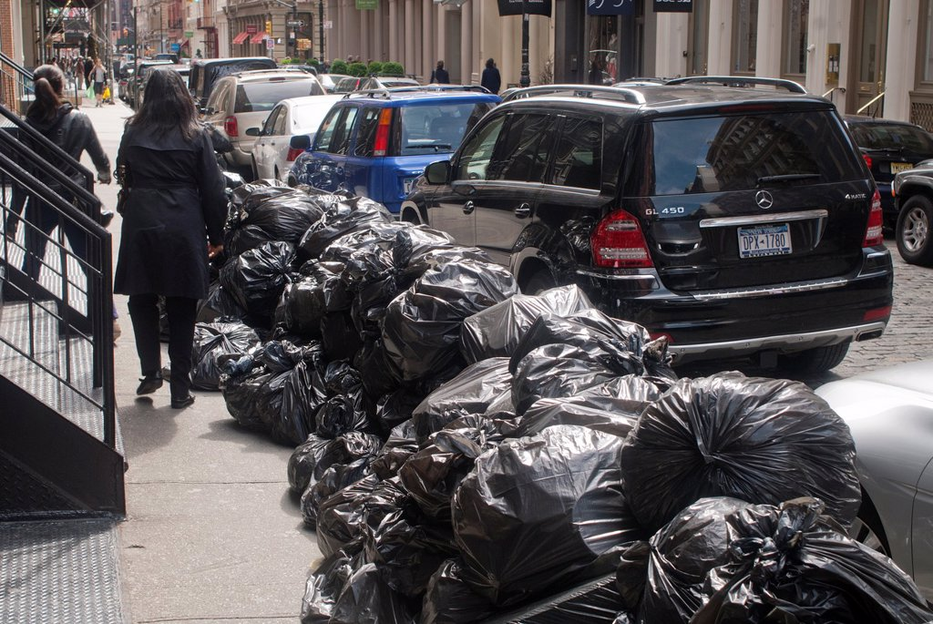 Stock Photo: 1566-986886 Piles of trash in plastic bags await pick-up curbside in New York