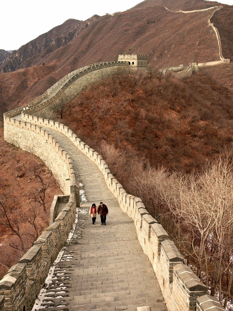 Stock Photo: 1566-987683 A couple dressed in winter coats walks on a section of the Great Wall of China near Beijing, China