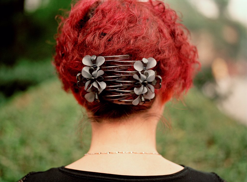 A portrait of the back of a Chinese woman´s head with bright red hair and large clips holding it in place, in a park : Stock Photo