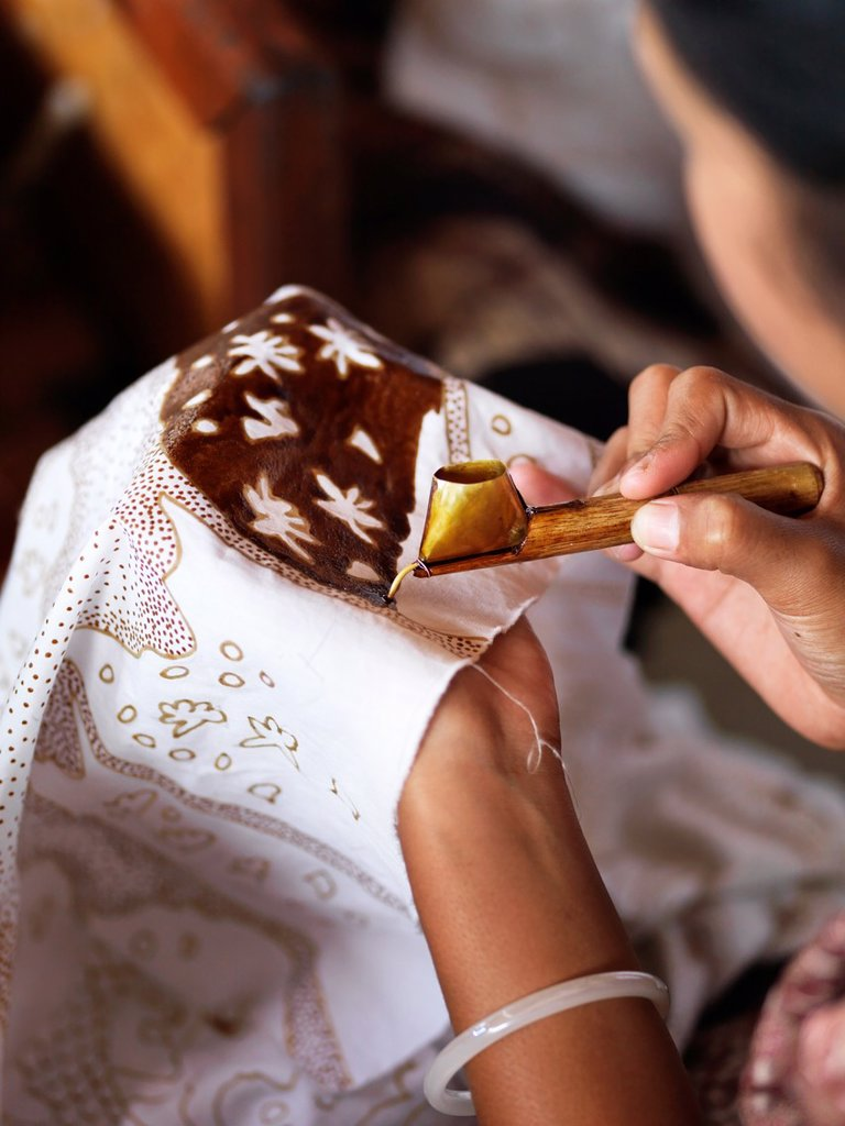 Stock Photo: 1566-987711 A woman applies liquid wax to a fabric with a canting, which is used in batik making Batik is a wax-resist dyeing technique used on textile