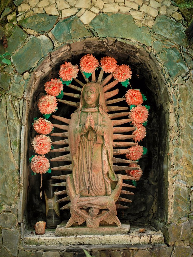 The jungles where Edward James built his Las Pozas - concrete buildings, bridges and pavilions around waterfalls in the 1960´s and 1970´s - enjoyed by locals today for the swimming in the waterfalls A detail of a patron saint : Stock Photo
