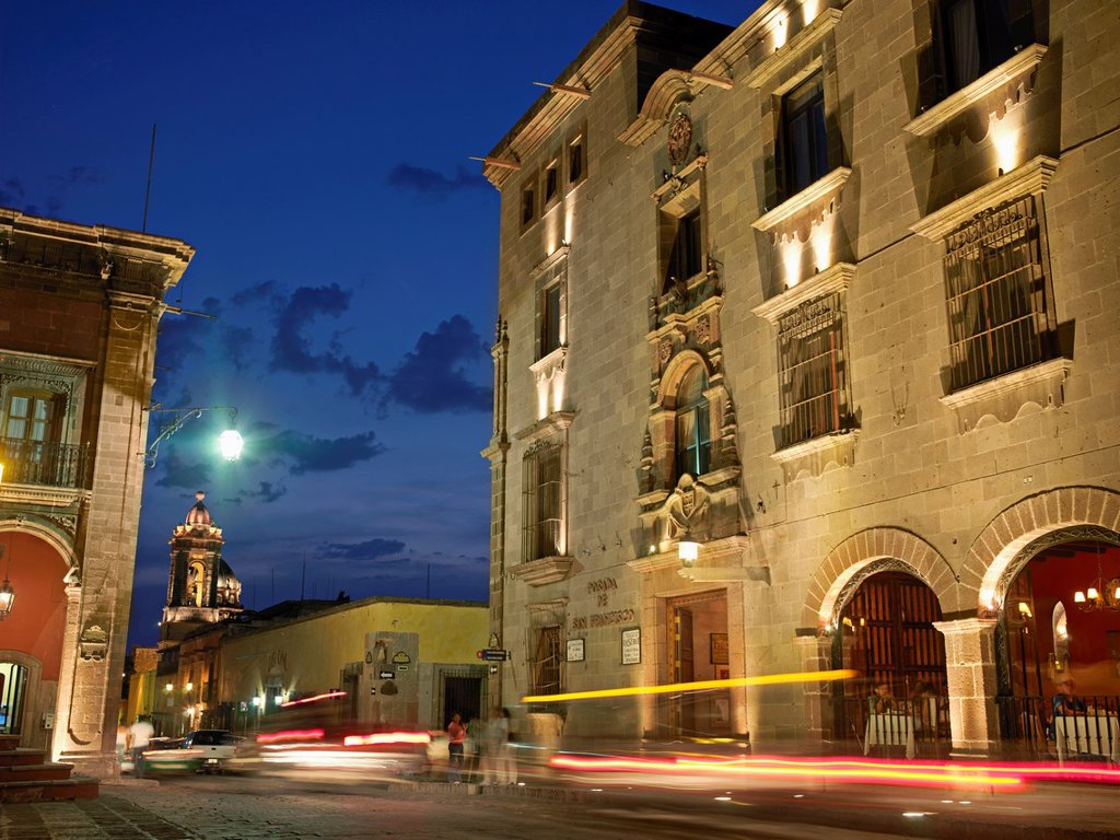 Stock Photo: 1566-987745 The facade of Posada San Francisco - a hotel in the center of town, illuminated at night by lights, with cars passing in front of it