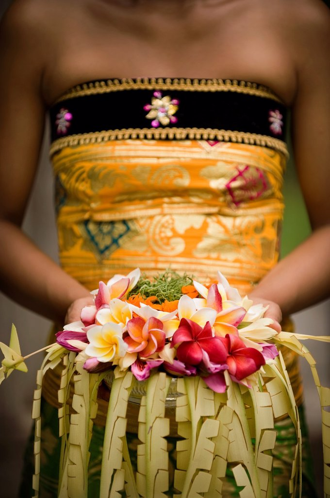A close-up of Balinese woman holding a floral arrangement : Stock Photo