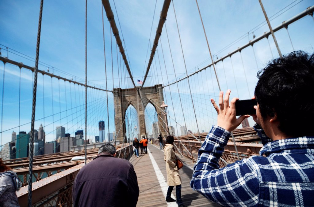 Young man photographs NYC Skyline from Brooklyn Bridge, with New World Trade Center : Stock Photo