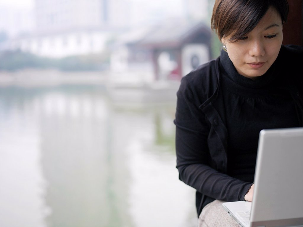 A Chinese business woman in a suit checking her email on her laptop through wireless internet with a lake and traditional Chinese architecture in the background : Stock Photo