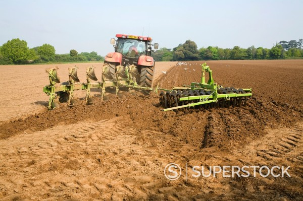 Stock Photo: 1566-993221 Red tractor ploughing field Shottisham, Suffolk, England