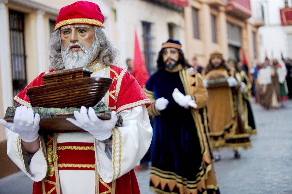 Stock Photo: 1566-993800 A man wearing a mask and costume representing Noah holds a miniature of an ark during an Easter Holy Week procession in Puente Genil, in the province of Cordoba, Andalusia.