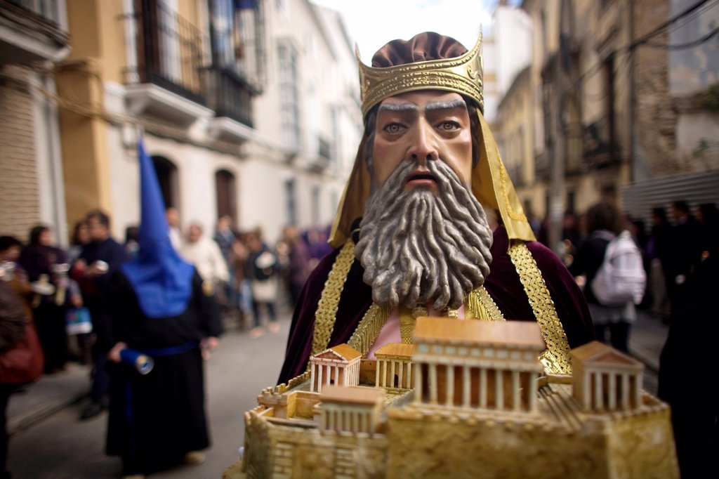 Stock Photo: 1566-993803 A masked man dressed as a biblical character holds a relic during an Easter Holy Week procession in Puente Genil, in the province of Cordoba, Andalusia, Spain.