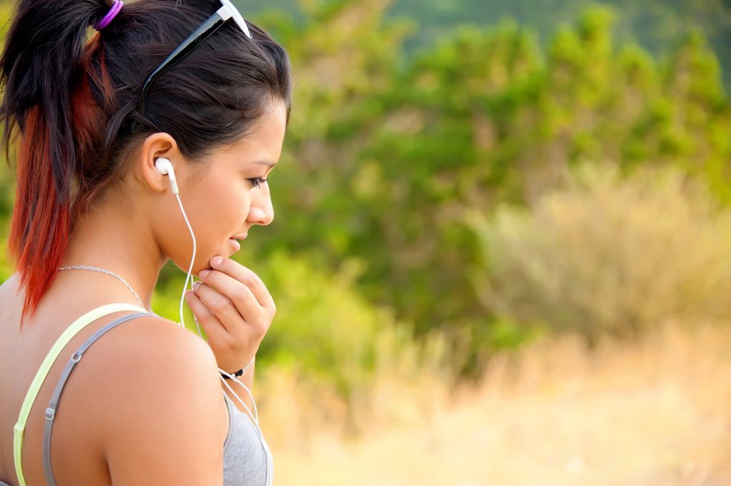 Young hispanic woman listening to music on her mp3 player : Stock Photo