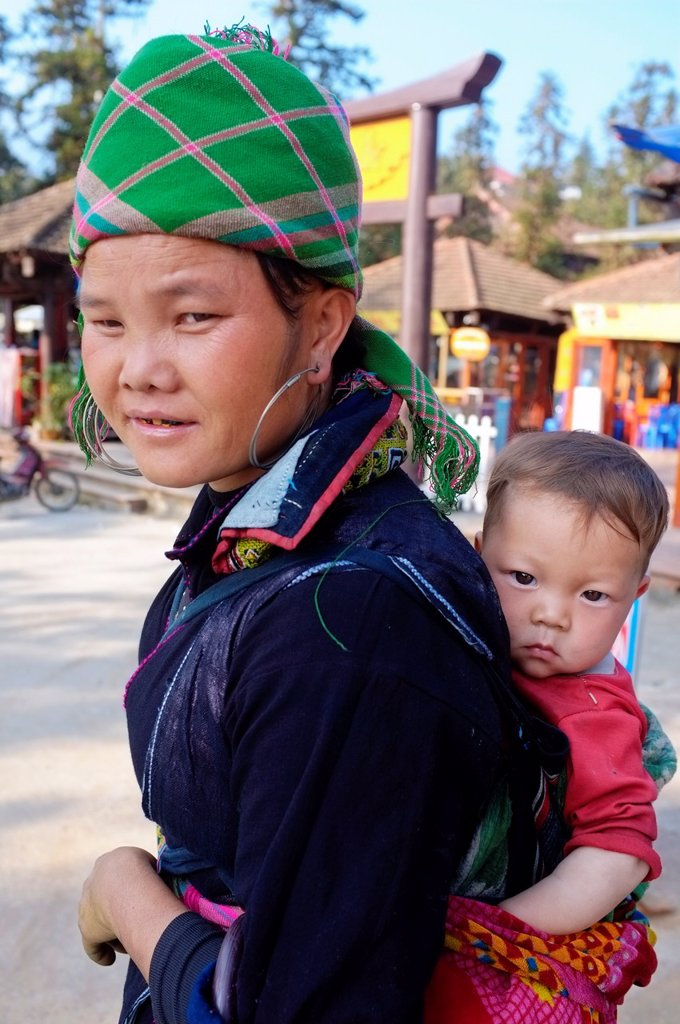Black Hmong woman carrying baby on her back, Sapa, North Vietnam : Stock Photo