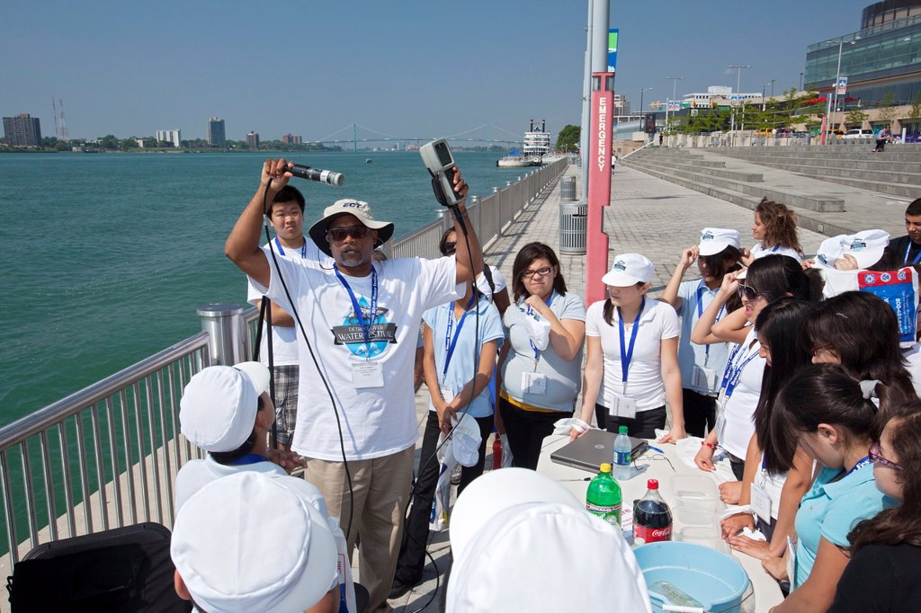 Stock Photo: 1566-997961 Detroit, Michigan - Sixth grade students learn about water quality at the Detroit River Water Festival  Here a teacher displays a meter they will use to test various characteristics of water from the Detroit River