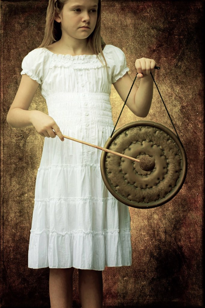 Girl in white dress strikes a gong : Stock Photo
