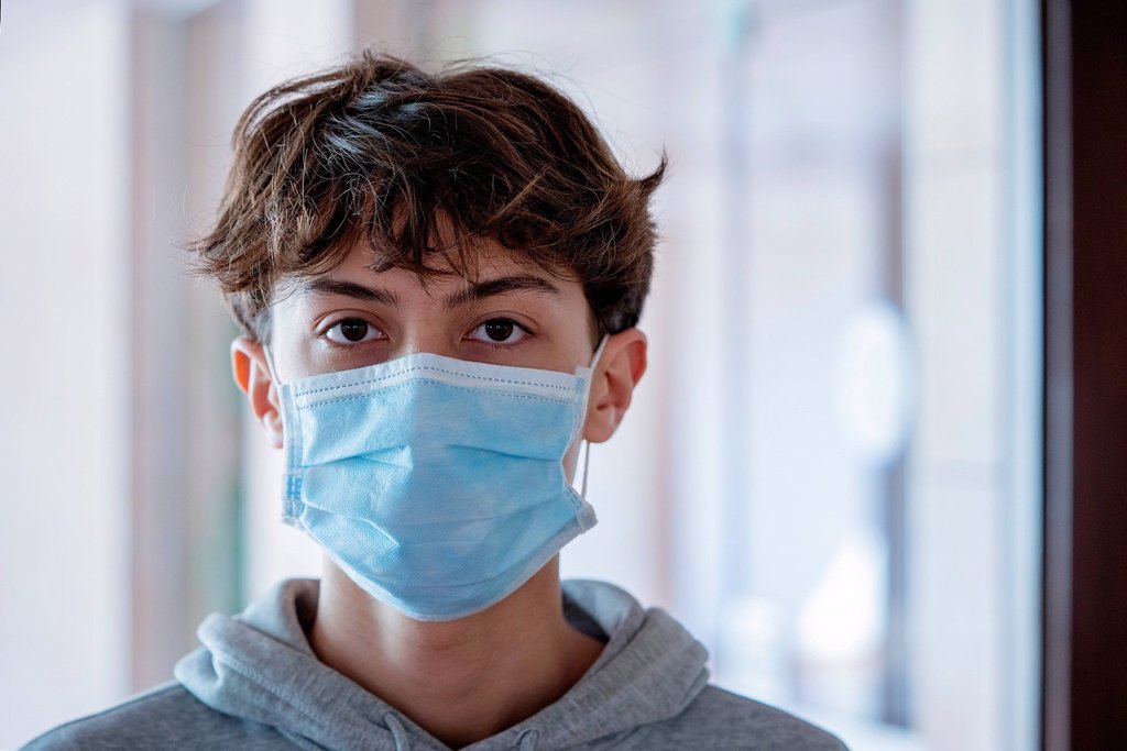 Stock Photo: 1569-16032389 Close up of teenage boy wearing blue surgical mask