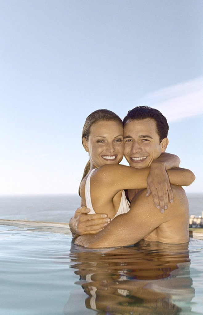 Young couple embracing in pool : Stock Photo