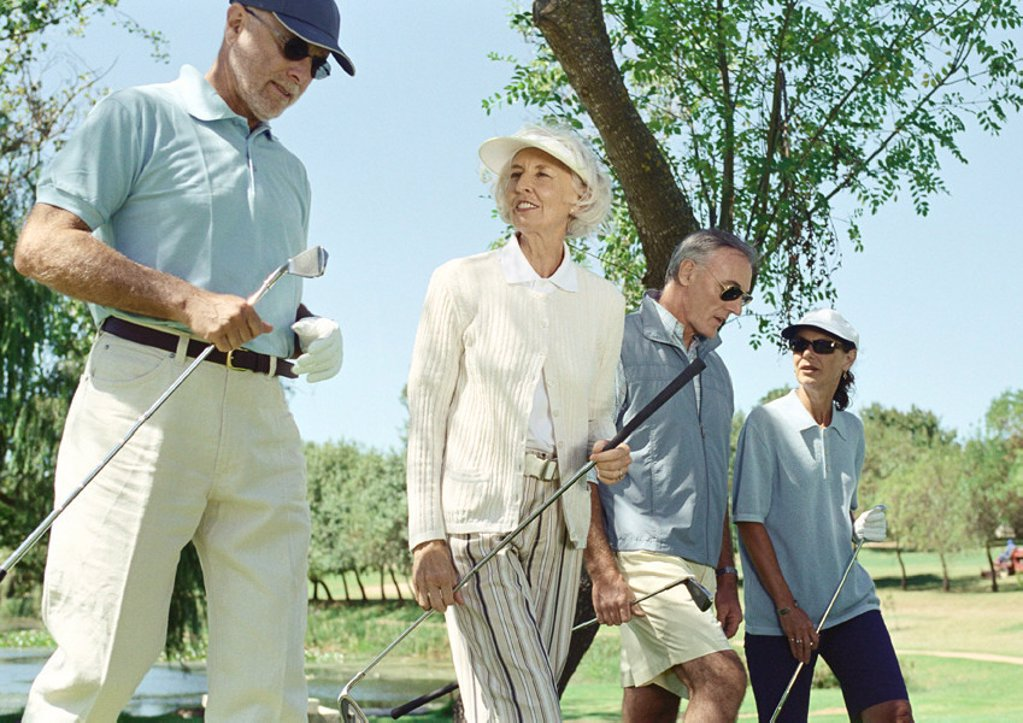 Mature golfers walking side by side : Stock Photo