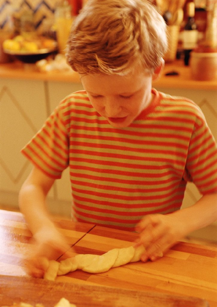 Child handling pastry dough, blurred motion : Stock Photo