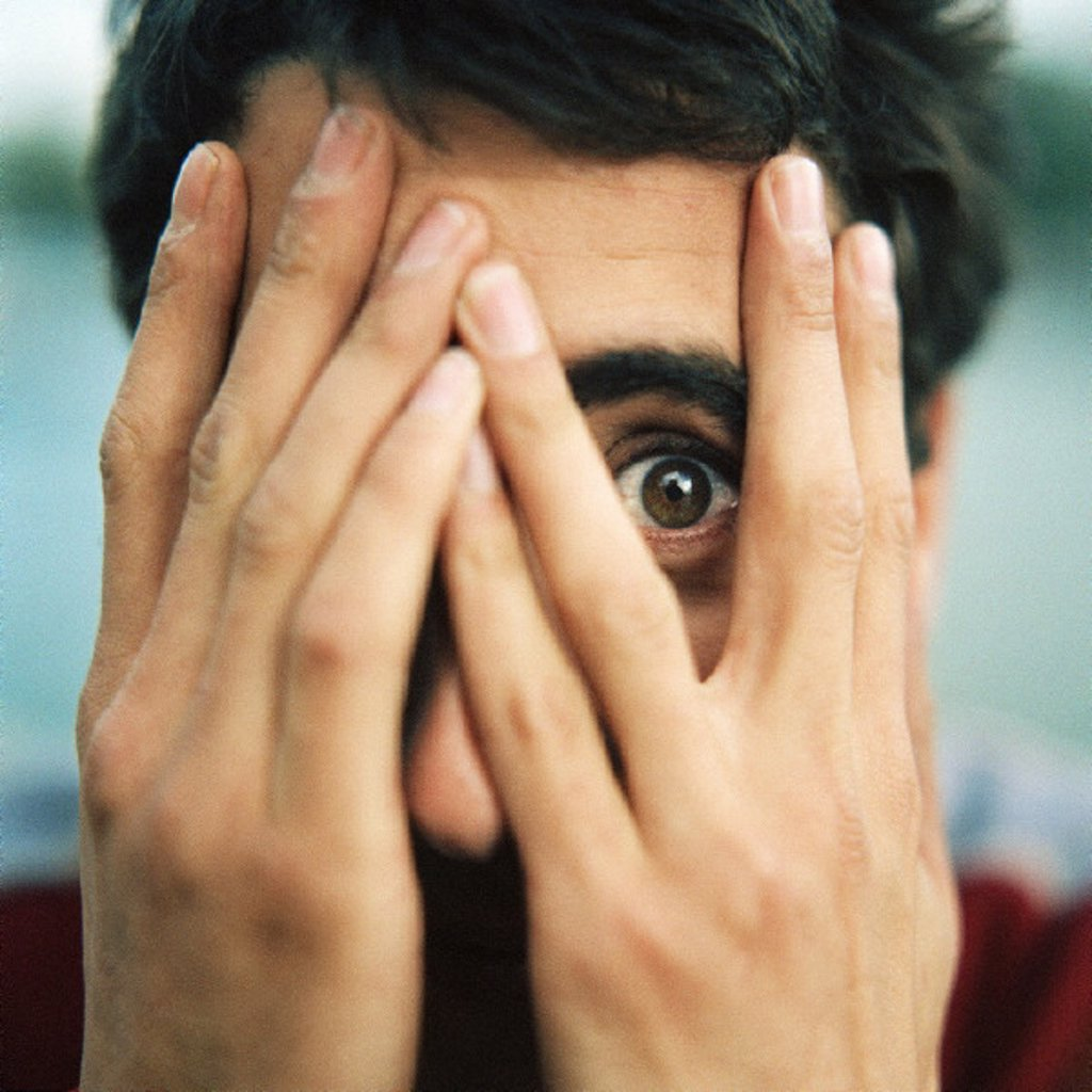Stock Photo: 1569R-106043 Young man with hands over face, looking through fingers with one eye, close-up