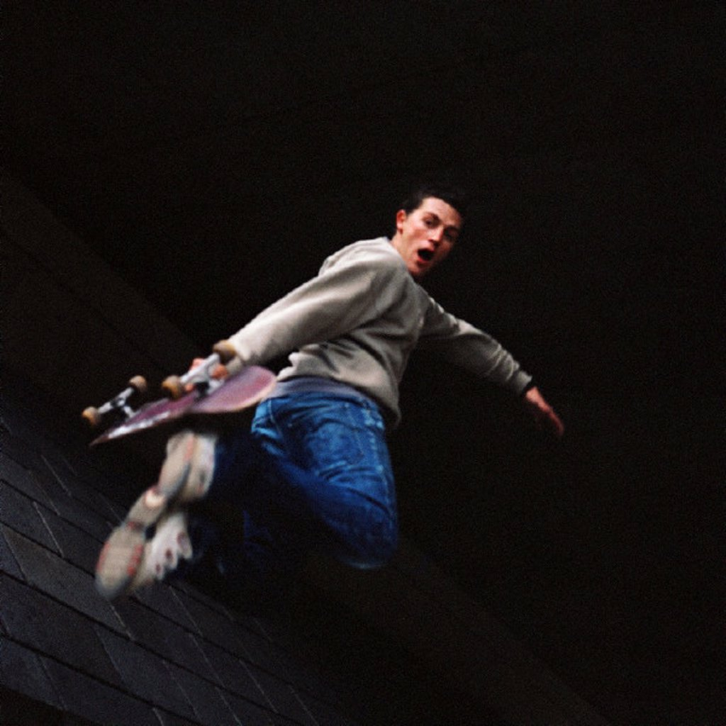 Young man in mid-air holding skateboard : Stock Photo