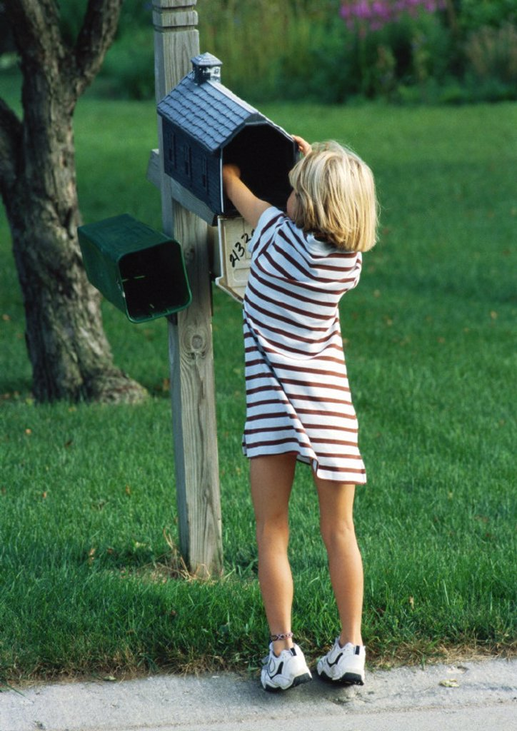 Girl with hand in mailbox, rear view : Stock Photo