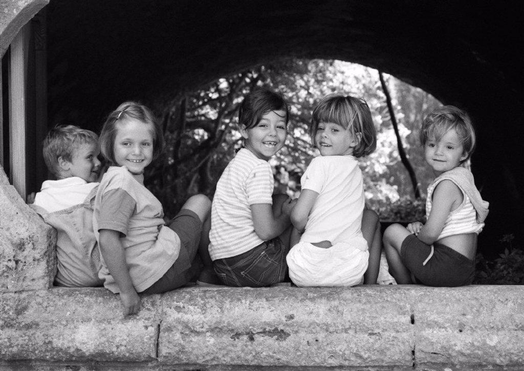 Five children sitting under an arch, b&w : Stock Photo