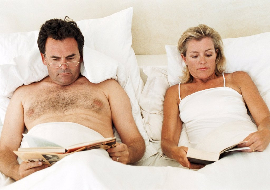 Stock Photo: 1569R-116011 Couple lying in bed, reading