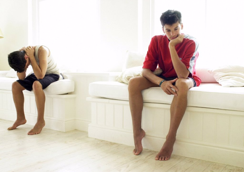 Two teenage boys sitting apart : Stock Photo