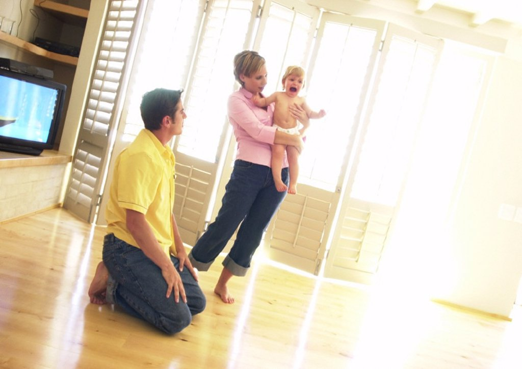 Woman holding crying baby, man kneeling on floor : Stock Photo