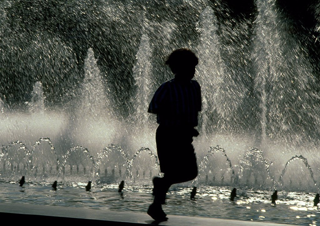 Silhouette of boy crouching on edge of fountain : Stock Photo