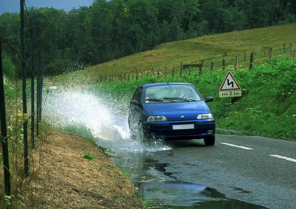 Stock Photo: 1569R-12026 Car driving through puddle, splashing water