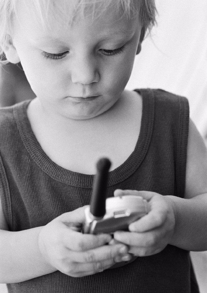 Child looking at phone, close-up, b&w : Stock Photo