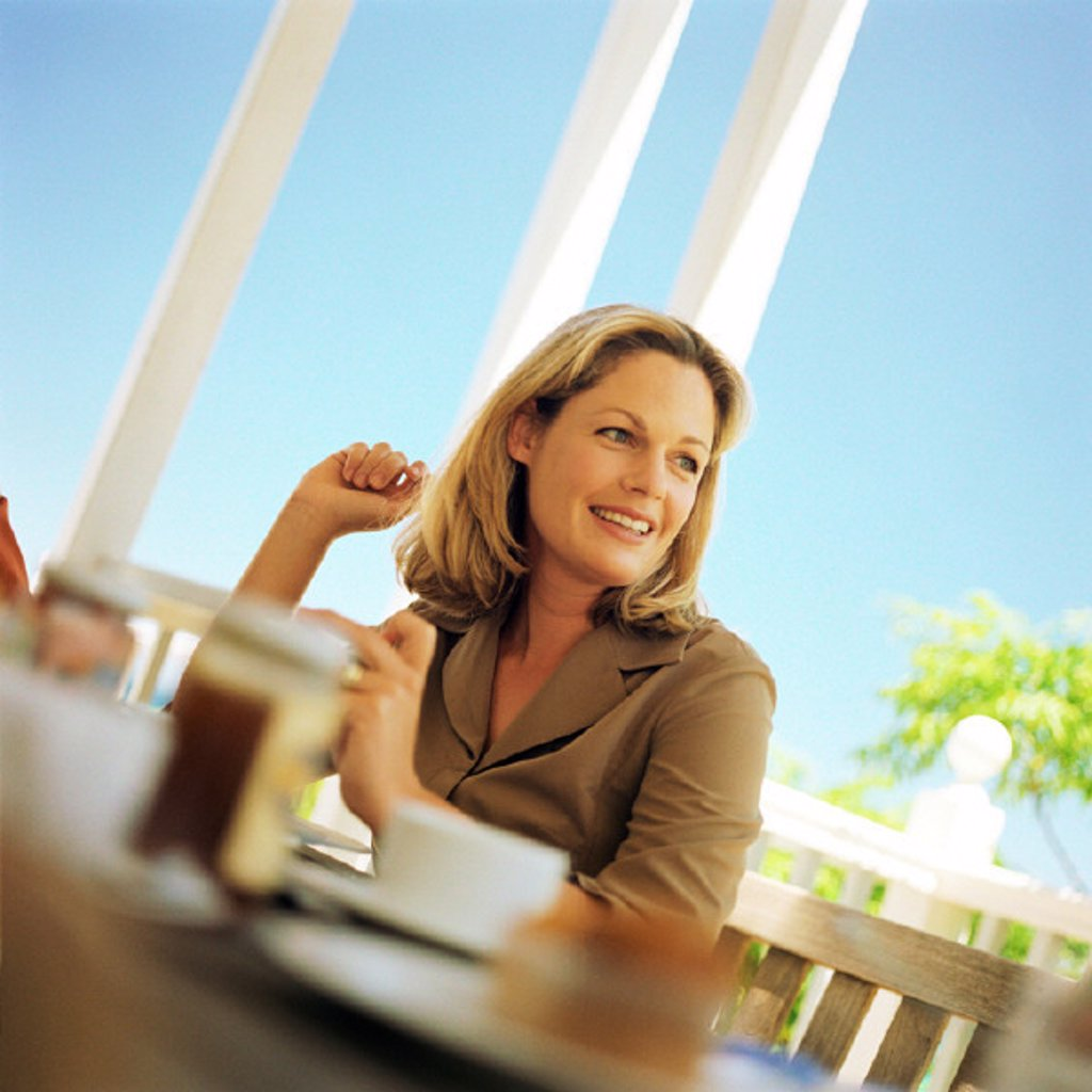 Stock Photo: 1569R-124066 Woman sitting at table, smiling