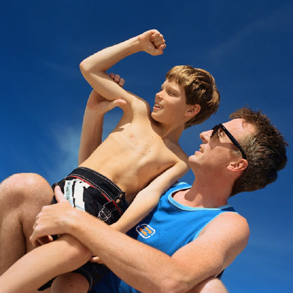 Father holding son, boy flexing arm, low angle view : Stock Photo
