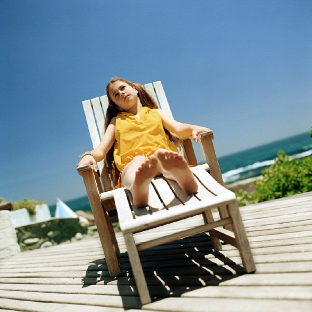 Stock Photo: 1569R-126062 Girl sitting in deckchair, sea in background