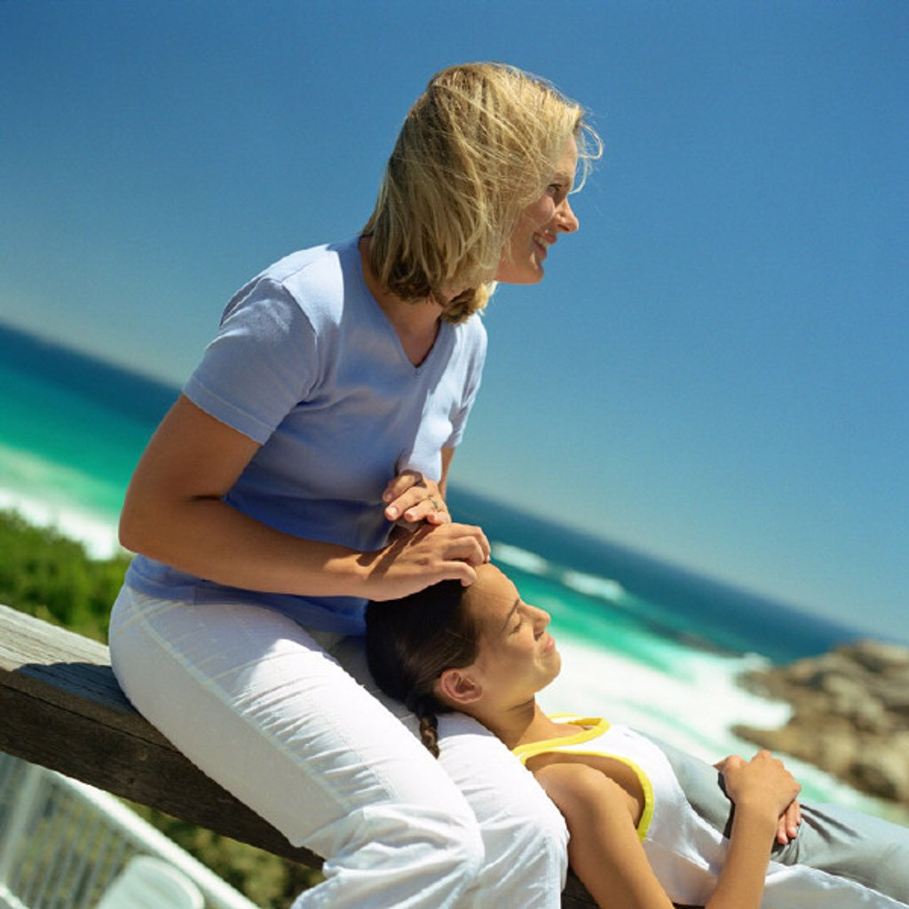 Girl with head on mother´s lap, sea in background : Stock Photo