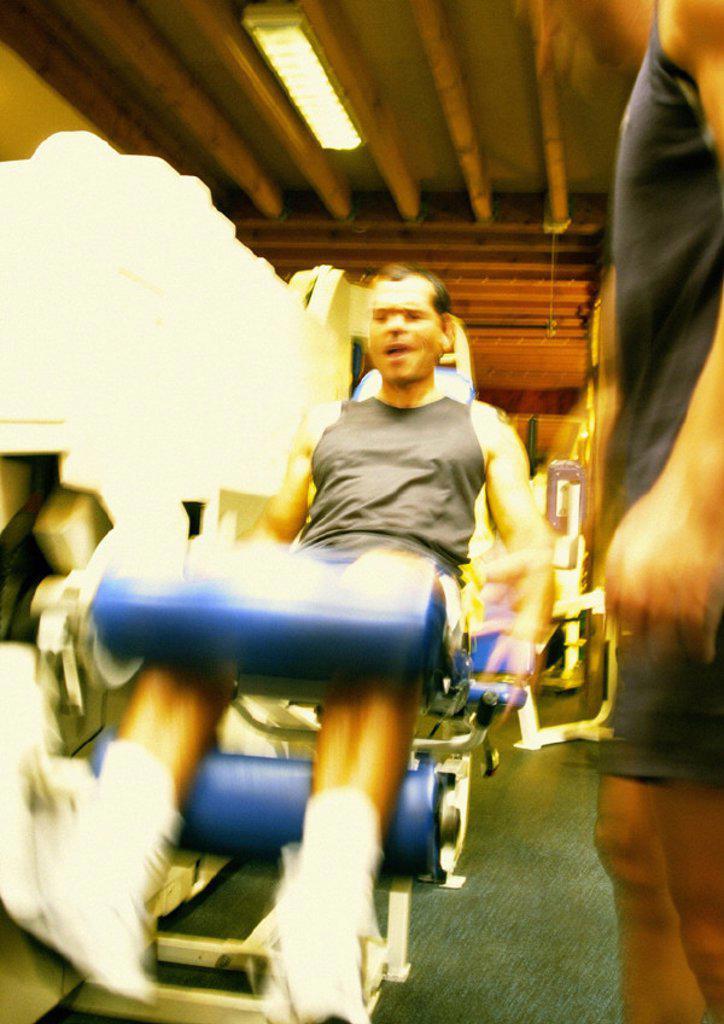 Stock Photo: 1569R-131020 Man using weight machine in gym