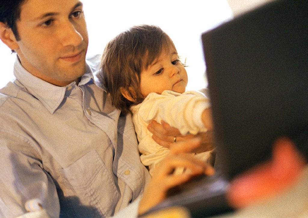 Father and baby, father using laptop, baby sitting on father´s lap : Stock Photo