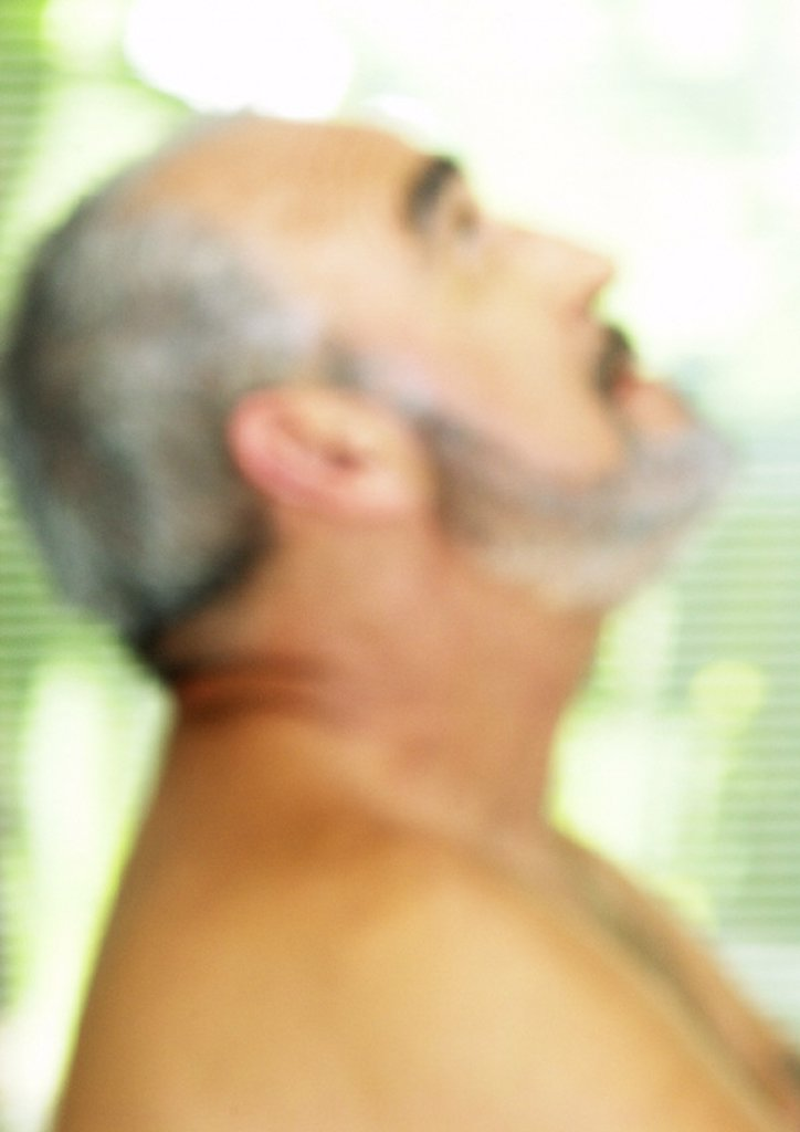 Stock Photo: 1569R-135041 Mature man looking up, side view, blurred