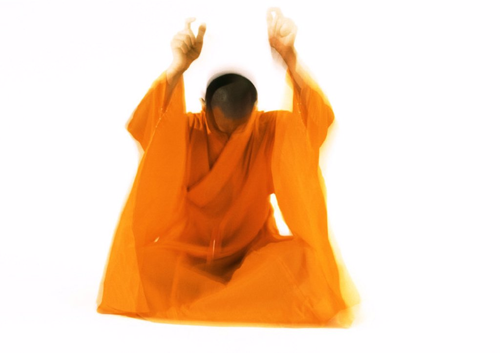 Buddhist monk meditating, blurred motion : Stock Photo