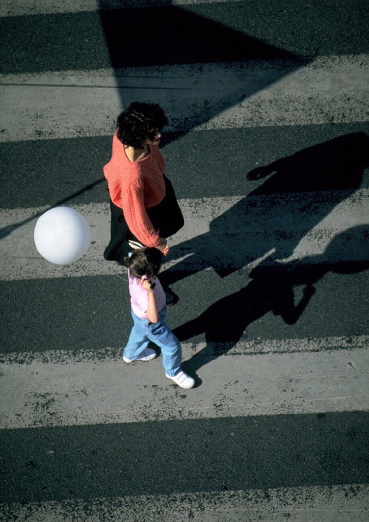 Woman and young girl holding balloon, walking on crosswalk, high angle view : Stock Photo