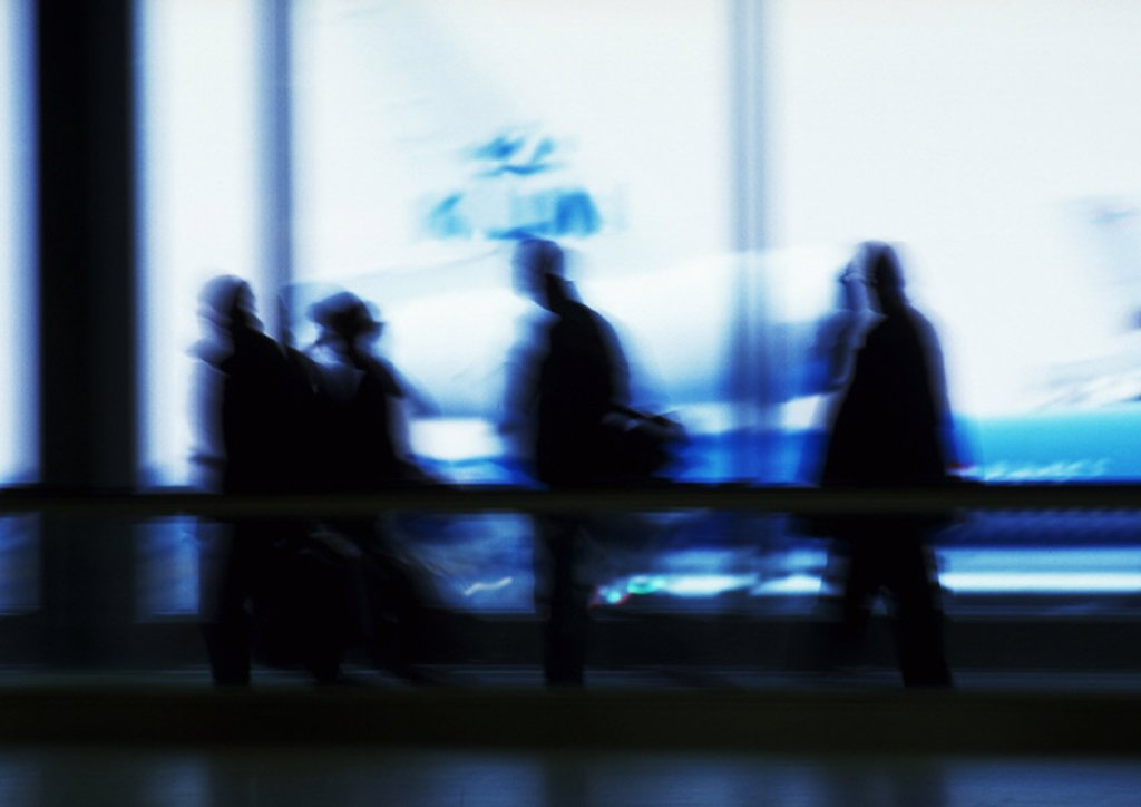 Stock Photo: 1569R-14066 Silhouette of people in airport in front of windows, blurred